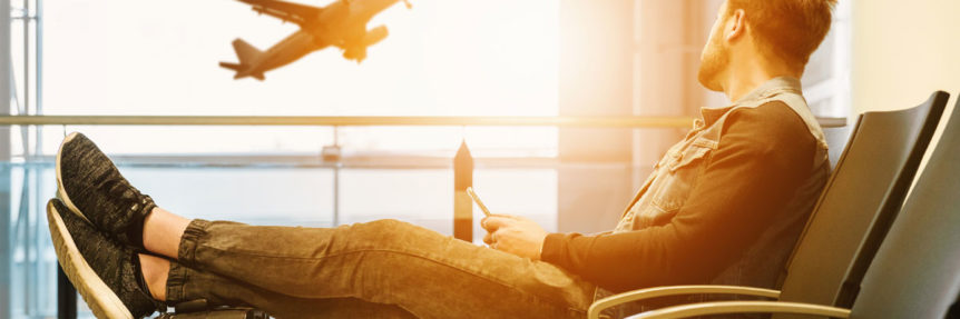 man sitting at airport lounge with plane outside window